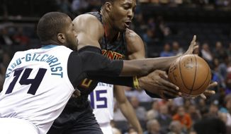 Atlanta Hawks' Dwight Howard, right, and Michael Kidd-Gilchrist, left, chase a loose ball during the first half of an NBA basketball game in Charlotte, N.C., Monday, March 20, 2017. (AP Photo/Chuck Burton)