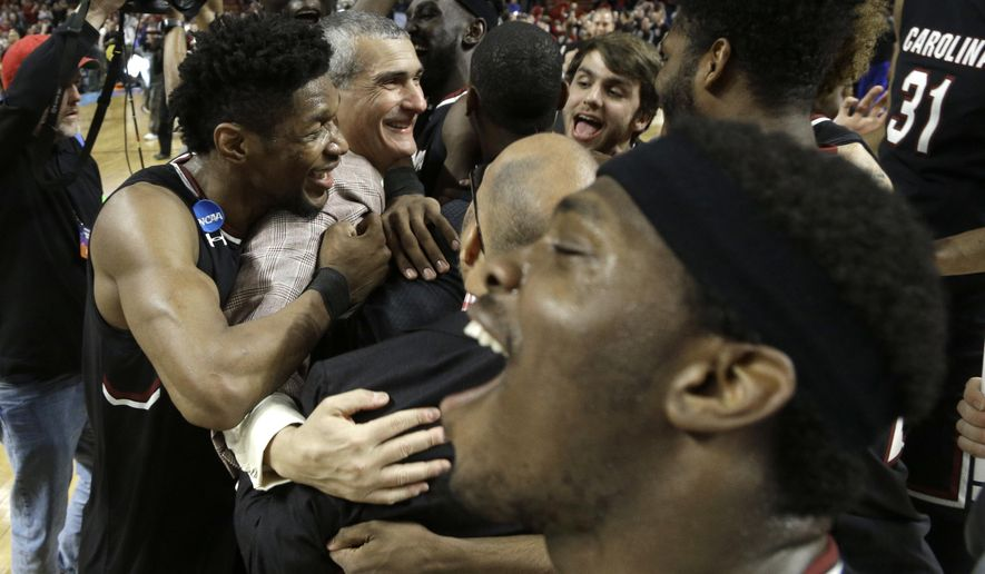South Carolina head coach Frank Martin, second from left, is hugged by Chris Silva, left, as they celebrate after a second-round game against Duke in the NCAA men's college basketball tournament in Greenville, S.C., Sunday, March 19, 2017. (AP Photo/Chuck Burton)