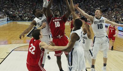 Wisconsin forward Nigel Hayes (10) goes to the basket against Villanova forward Darryl Reynolds, left, guard Donte DiVincenzo (10) and Mikal Bridges, center,during the second half of a second-round men's college basketball game in the NCAA Tournament, Saturday, March 18, 2017, in Buffalo, N.Y. (AP Photo/Bill Wippert)