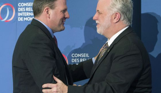 New Hampshire Gov. Chris Sununu, left, greets Quebec Premier Philippe Couillard after being introduced at a foreign relations luncheon Monday, March 20, 2017 in Montreal. Sununu is in Quebec to discuss the economic relationship between the two and meet with business, political and community leaders.(Ryan Remiorz/The Canadian Press via AP)