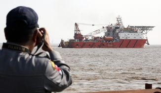 "A Myanmar police officer takes a photo of a Malaysian ship arriving at Thilawa port in Yangon, Myanmar, Thursday, Feb. 9, 2017. The ""Food Flotilla for Myanmar"" carrying 2,300 tons of food and medicine to help members of Myanmar's persecuted Muslim Rohingya minority arrived in Yangon as rights groups accuse the army of mass killings, rapes and other crimes targeting the ethnic group. (AP Photo/Thein Zaw)"