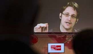 Edward Snowden, a former CIA worker before turning whistleblower, speaks via satellite at the IT fair CeBIT in Hanover, Germany, Tuesday March 21,  2017. ( Friso Gentsch/dpa via AP)