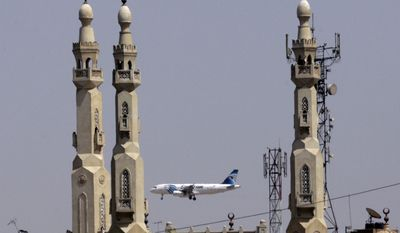 FILE - In this May 21, 2016, file photo, an EgyptAir plane flies past minarets of a mosque as it approaches Cairo International Airport, in Cairo, Egypt. A new U.S. security measure targeting flights from eight mostly Muslim countries is leading travelers to reconsider their plans to fly through some airports in the Middle East. An electronics ban affects flights from international airports to the U.S. from in Amman, Jordan; Kuwait City, Kuwait; Cairo; Istanbul; Jeddah and Riyadh, Saudi Arabia; Casablanca, Morocco; Doha, Qatar; and Dubai and Abu Dhabi in the United Arab Emirates. (AP Photo/Amr Nabil, File)