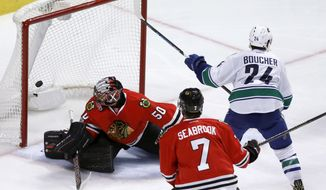 Vancouver Canucks' Reid Boucher (24) scores past Chicago Blackhawks goalie Corey Crawford (50) as Brent Seabrook watches during the second period of an NHL hockey game Tuesday, March 21, 2017, in Chicago. (AP Photo/Charles Rex Arbogast)