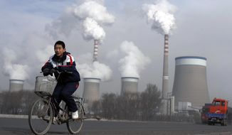 FILE - In this Dec. 3, 2009 file photo, a Chinese boy cycles past cooling towers of a coal-fired power plant in Dadong, Shanxi province, China. Led by cutbacks in China and India, construction of new coal-fired power plants is falling worldwide, improving chances climate goals can be met despite earlier pessimism, three environmental groups said Wednesday, March 22, 2017. (AP Photo/Andy Wong, File)