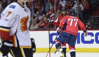Washington Capitals right wing T.J. Oshie (77) celebrates his goal with left wing Alex Ovechkin (8) as Calgary Flames defenseman T.J. Brodie (7) skates by during the second period of an NHL hockey game, Tuesday, March 21, 2017, in Washington. (AP Photo/Molly Riley)