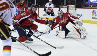 Washington Capitals defenseman Karl Alzner (27) defends the net with goalie Braden Holtby (70) against Calgary Flames right wing Kris Versteeg (10), far left, during the first period of an NHL hockey game, Tuesday, March 21, 2017, in Washington. (AP Photo/Molly Riley)