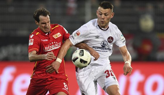 Berlin's Stephan Fuerstner, left, and Nuremberg's Kevin Moehwald in action during the 2nd Bundesliga soccer match between 1. FC Union Berlin and 1. FC'Nuremberg at the Stadion An der Alten Foersterei in Berlin, Germany, Monday, March 20, 2017. (Soeren Stache/dpa via AP)