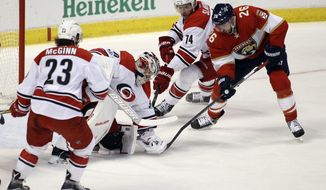 Carolina Hurricanes goalie Cam Ward, center, holds the puck on Florida Panthers' Thomas Vanek, of Austria (26) as teammates Brock McGinn (23) and Jaccob Slavin (74) defend during the first period of an NHL hockey game, Tuesday, March 21, 2017, in Sunrise, Fla. (AP Photo/Luis M. Alvarez)