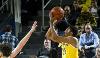 FILE - In this Jan. 7, 2017, file photo, Michigan guard Zak Irvin (21) shoots a three point basket in the first half of an NCAA college basketball game against Maryland, in Ann Arbor, Mich. The Wolverines have made a school record 340 3s this season, their top six scorers are all capable of making shots from beyond the arc and even 6-foot-11 Moe Wagner and 6-10 D.J. Wilson can make long-range jumpers. (AP Photo/Tony Ding, File)