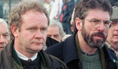 FILE - This is a Sunday, Feb. 1, 1998 file photo of Martin McGuinness, the Sinn Fein Chief Negotiator, left, and Sinn Fein's president Gerry Adams as they participate in the Bloody Sunday anniversary march in Londonderry, Northern Ireland.  McGuinness, an IRA and Sinn Fein leader who became a minister of peacetime Northern Ireland, has died, according to UK media Tuesday, March 21, 2017 .  (AP Photo/Paul McErlane, File)