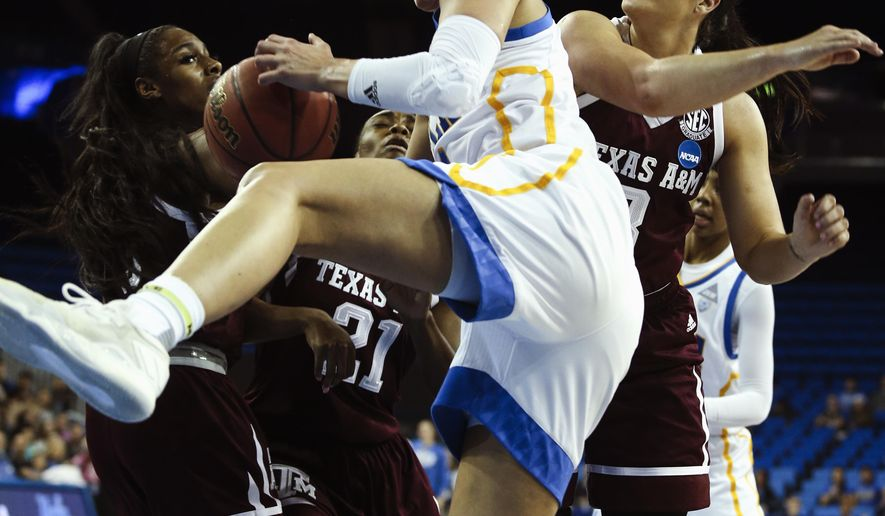 UCLA guard Nicole Lornet, center, fights for a rebound with Texas A&M during the first half of a second-round game in the NCAA women's college basketball tournament, Monday, March 20, 2017, in Los Angeles. (AP Photo/Ringo H.W. Chiu)