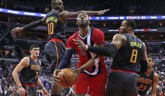Washington Wizards guard John Wall (2) shoots between Atlanta Hawks forward Ersan Ilyasova (7), guard Tim Hardaway Jr. (10) and center Dwight Howard (8) during the second half of an NBA basketball game Wednesday, March 22, 2017, in Washington. The Wizards won 104-100. (AP Photo/Alex Brandon)