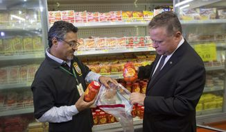 Brazil's Agriculture Minister Blairo Maggi, right, accompanied by a sanitary inspection agent, collect meat products for testing, in a supermarket in Brasilia, Brazil, Wednesday, March 22, 2017. South Africa is partially suspending imports of Brazilian meat, the latest country to do so in the wake of an inspection scandal. Brazilian investigators charge that health inspectors in the South American country were bribed to overlook the sale of expired meats and chemicals and other products were added to meat to improve its appearance and smell. (AP Photo/Eraldo Peres)