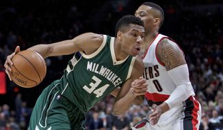 Milwaukee Bucks forward Giannis Antetokounmpo, left, dribbles past Portland Trail Blazers guard Damian Lillard during the first half of an NBA basketball game in Portland, Ore., Tuesday, March 21, 2017. (AP Photo/Craig Mitchelldyer)