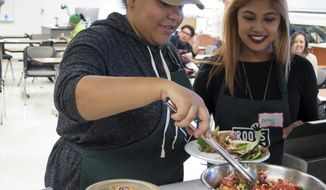 ADVANCE FOR RELEASE SATURDAY, MARCH 25, 2017, AT 12:01 A.M. CDT. AND THEREAFTER - In this March 4, 2017 photo, Alexus Kloetzke-Wilson, left, and Krystal Aviles are tasting salads created by other students in Twin Cities gardening programs in Minneapolis. Roots for the Home Team is a nonprofit founded by Susan Moores, a dietician. Her organization buys produce directly from local gardens, recruits young people from those programs to make unique salad recipes, then pays them to sell their product at sports venues or at grocery stores like Kowalski's. (Doualy Xaykaothao/Minnesota Public Radio via AP)