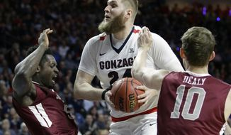 FILE - In this March 6, 2017, file photo, Gonzaga's Przemek Karnowski, center, drives into Santa Clara's Emmanuel Ndumanya, left, during the first half of a West Coast Conference tournament NCAA college basketball game, in Las Vegas. Santa Clara's Kai Healy is on the right.  Karnowski's back became so bad last season the question wasn't whether he'd play basketball again, but if he would be able to walk without pain. A year later, he's healthy and leading the Zags into the Sweet 16. (AP Photo/John Locher, File)