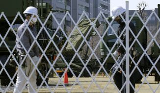 Workers set up a fence around the PAC-3 Patriot missile unit deployed against North Korea's missile firing at the Defense Ministry in Tokyo, Wednesday, March 22, 2017. North Korea's latest missile launch Wednesday appears to have ended in a failure. That's what South Korean defense officials say, three days after the North claimed a major breakthrough in its rocket development program. (AP Photo/Shizuo Kambayashi)