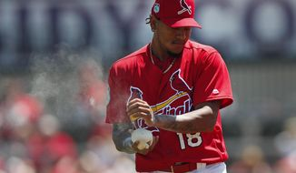 St. Louis Cardinals starting pitcher Carlos Martinez (18) uses a rosin bag as he prepares to pitch in the first inning of a spring training baseball game against the Washington Nationals Wednesday, March 22, 2017, in Jupiter, Fla. (AP Photo/John Bazemore)