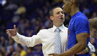 FILE- In this Jan. 25, 2017, file photo, Florida head coach Mike White talks with forward Justin Leon during the first half of an NCAA college basketball game in Baton Rouge, La. White has the Gators two wins away from the Final Four. (AP Photo/Bill Feig, File)