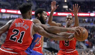 Chicago Bulls' Jimmy Butler (21) strips the ball from Detroit Pistons' Andre Drummond as Rajon Rondo (9) also defends during the first half of an NBA basketball game Wednesday, March 22, 2017, in Chicago. (AP Photo/Charles Rex Arbogast)