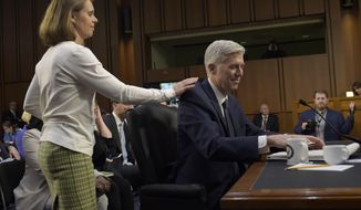 Marie Louise Gorsuch, wife of Supreme Court Justice nominee Neil Gorsuch touches his shoulder during a break in testimony on Capitol Hill in Washington, Wednesday, March 22, 2017, during his confirmation hearing before the Senate Judiciary Committee. (AP Photo/Susan Walsh)