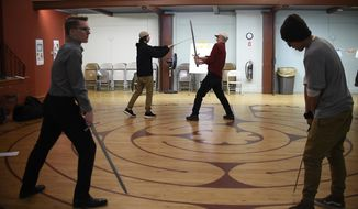 "In this Thursday, March 2, 2017 photo, Kevin Coleman, right rear, director of education at Shakespeare & Co., works with a teenage man, left rear, playing the role of a soldier, as another young man, left front, portraying Macbeth, practices a sword fight with another young man, right front, portraying Macduff during a rehearsal for Shakespeare's ""Macbeth,"" in Pittsfield, Mass. Shakespeare & Company, a theater company in Lenox, Massachusetts, works with the courts to get youngsters who run afoul of the law sentenced to perform works of Shakespeare onstage as an alternative to community service or juvenile detention. (AP Photo/Jessica Hill)"