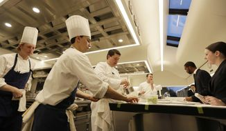 In this photo taken Thursday, March 9, 2017, servers wait for dishes being brought to the pass inside the new kitchen at the French Laundry restaurant in Yountville, Calif. Celebrated chef Thomas Keller has just opened a state-of-the art new kitchen at his famed French Laundry after spending $10 million on an extensive renovation. Unlike the stainless steel austerity of most commercial kitchens, this one is white, spacious and sunlit by skylights and two walls of wraparound windows overlooking the garden. (AP Photo/Eric Risberg)