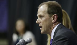 Mike Hopkins talks to reporters after he was introduced as Washington's new NCAA college basketball head coach, Wednesday, March 22, 2017, in Seattle. Hopkins, a longtime Syracuse assistant coach, replaces Lorenzo Romar. (AP Photo/Ted S. Warren)
