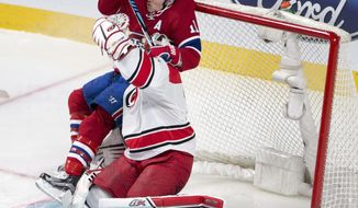 Montreal Canadiens right wing Brendan Gallagher (11) runs into Carolina Hurricanes goalie Eddie Lack (31) during the second period of an NHL hockey game Thursday, March 23, 2017, in Montreal. (Ryan Remiorz/The Canadian Press via AP)