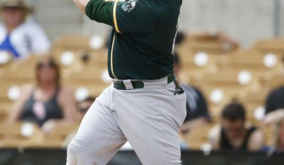 Oakland Athletics' Stephen Vogt follows through his swing, a two-run double, against the Chicago White Sox during the first inning of a spring training baseball game Wednesday, March 22, 2017, in Glendale, Ariz. (AP Photo/Ross D. Franklin)