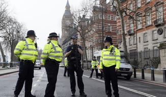 Police officers stand guard on a road leading to the Houses of Parliament in London, Thursday March 23, 2017 on her way to the House of Parliament. On Wednesday a man went on a deadly rampage, first driving a car into pedestrians then stabbing a police officer to death before being fatally shot by police within Parliament's grounds in London. (AP Photo/Kirsty Wigglesworth)