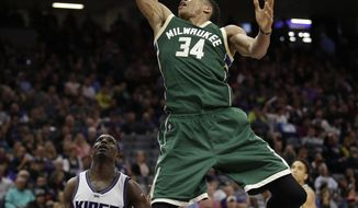 Milwaukee Bucks forward Giannis Antetokounmpo goes to the basket over Sacramento Kings guard Darren Collison during the first half of an NBA basketball game, Wednesday, March 22, 2017, in Sacramento, Calif. (AP Photo/Rich Pedroncelli)