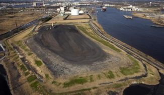 FILE - This Friday, Feb. 29, 2008, photo shows an aerial view of the fly ash landfill at Dominion's Chesapeake Energy Center in Chesapeake, Va. Millions of tons of ash stored at the former coal-fired power plant in the city will become increasingly vulnerable to flooding and other coastal risks. Virginia and its public utilities struggle to cope with the coal ash buried in pits and ponds across the state, tons more of the industrial byproduct is being imported each year. (Bill Tiernan/The Virginian-Pilot via AP)