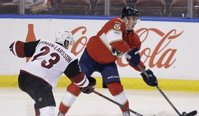 Florida Panthers right wing Reilly Smith (18) controls the puck as Arizona Coyotes defenseman Oliver Ekman-Larsson (23) defends during the first period of an NHL hockey game, Thursday, March 23, 2017, in Sunrise, Fla. (AP Photo/Terry Renna)
