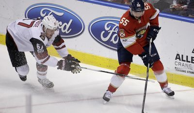 Arizona Coyotes left wing Lawson Crouse (67) and Florida Panthers defenseman Jason Demers (55) battle for the puck during the first period of an NHL hockey game, Thursday, March 23, 2017, in Sunrise, Fla. (AP Photo/Terry Renna)
