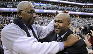 FILE - In this March 9, 2013, file photo, former Georgetown coach John Thompson Jr., left, congratulates his son Georgetown head coach John Thompson III, right, after the Hoya's 61-39 win over Syracuse in an NCAA college basketball game in Washington.  Georgetown has fired basketball coach John Thompson III on Thursday, March 23, 2017, after two consecutive losing seasons at the school his father led to a national championship. (AP Photo/Nick Wass, File) **FILE**