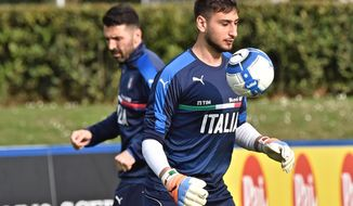 Italian national soccer team goalkeepers Gianluigi Buffon, left,  and Gianluigi Donnarumma warm up during a training session in Coverciano, near Florence, Italy, Wednesday, March 22, 2017. Italy will face Albania for a World Cup Group G qualifying soccer match in Palermo on Friday, March 24. (Maurizio Degl'Innocenti/ANSA via AP)