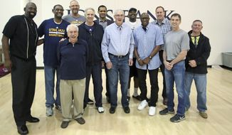 Former Utah Jazz coach Jerry Sloan, center, poses for a photograph with his team from 1997, following media interviews at the NBA basketball team's practice facility Wednesday, March 22, 2017, in Salt Lake City. The Jazz team that reached the 1997 NBA Finals was scheduled to attend a 20-year reunion celebration during halftime between the New York Knicks and the Jazz later Wednesday. (AP Photo/Rick Bowmer)