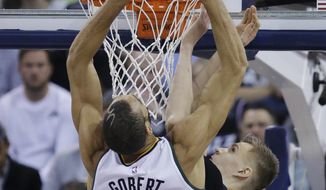 New York Knicks forward Kristaps Porzingis, rear, defends Utah Jazz center Rudy Gobert (27) during the first half of an NBA basketball game Wednesday, March 22, 2017, in Salt Lake City. (AP Photo/Rick Bowmer)