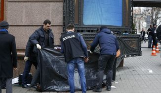 Forensic experts and police officers examine the scene following the killing of Denis Voronenkov in Kiev, Ukraine, Thursday, March 23, 2017. Ukrainian police said Voronenkov was shot dead Thursday by an unidentified gunman at the entrance of an upscale hotel in the Ukrainian capital. Voronenkov, 45, a former member of the communist faction in the lower house of Russian parliament, had moved to Ukraine last fall and had been granted Ukrainian citizenship. (AP Photo/Sergei Chuzavkov)
