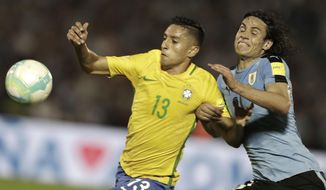 Uruguay's Edinson Cavani, center, heads the ball away from Brazil's Marquinhos, left, during a 2018 World Cup qualifying soccer match in Montevideo, Uruguay, Thursday, March. 23, 2017. (AP Photo/Natacha Pisarenko)