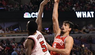 Philadelphia 76ers forward Dario Saric (9) shoots over Chicago Bulls forward Bobby Portis (5) during the first half of an NBA basketball game in Chicago, Friday, March 24, 2017. (AP Photo/David Banks)