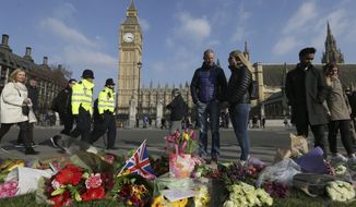 People view floral tributes to victims of Wednesday's attack outside the Houses of Parliament in London, Friday, March 24, 2017. On Thursday authorities identified a 52-year-old Briton as the man who mowed down pedestrians and stabbed a policeman to death outside Parliament in London, saying he had a long criminal record and once was investigated for extremism  but was not currently on a terrorism watch list. (AP Photo/Tim Ireland)