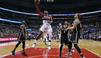 Washington Wizards guard John Wall (2) shoots between Brooklyn Nets guard Isaiah Whitehead, left, guard Spencer Dinwiddie (8) and center Justin Hamilton, right, during the second half of an NBA basketball game Friday, March 24, 2017, in Washington. (AP Photo/Alex Brandon)