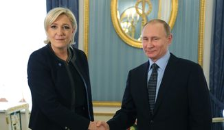 Russian President Vladimir Putin, right, shakes hands with French far-right presidential candidate Marine Le Pen, in the Kremlin in Moscow, Russia, Friday, March 24, 2017. Le Pen has made multiple visits to Russia, as have her father, niece and other members of the National Front, often meeting with Russian legislators. (Mikhail Klimentyev, Sputnik, Kremlin Pool Photo via AP)