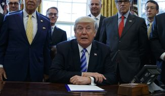 President Donald Trump, flanked by Commerce Secretary Wilbur Ross, left, and Energy Secretary Rick Perry, announces the approval of a permit to build the Keystone XL pipeline, clearing the way for the $8 billion project, Friday, March 24, 2017, in the Oval Office of the White House in Washington. (AP Photo/Evan Vucci)