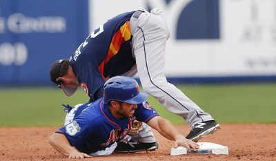 New York Mets' Travis d'Arnaud is safe at second after an error by Houston Astros shortstop Reid Brignac, top, on a Noah Syndergraad ground ball in the third inning of a spring training baseball game, Friday, March 24, 2017, in Port St. Lucie, Fla. (AP Photo/John Bazemore)