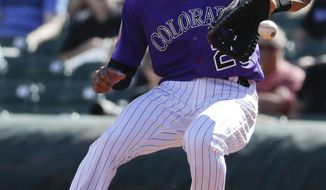 FILE - This March 4, 2017, file photo shows Colorado Rockies first baseman Ian Desmond fields a ball during the first inning at a spring baseball game in Scottsdale, Ariz. Desmond joined the Rockies after one season at Texas. (AP Photo/Chris Carlson, File)