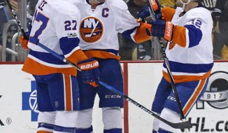 New York Islanders' Anders Lee (27) celebrates his goal with John Tavares (91) and Josh Bailey (12) during the second period of the team's NHL hockey game against the Pittsburgh Penguins in Pittsburgh, Friday, March 24, 2017. (AP Photo/Gene J. Puskar)